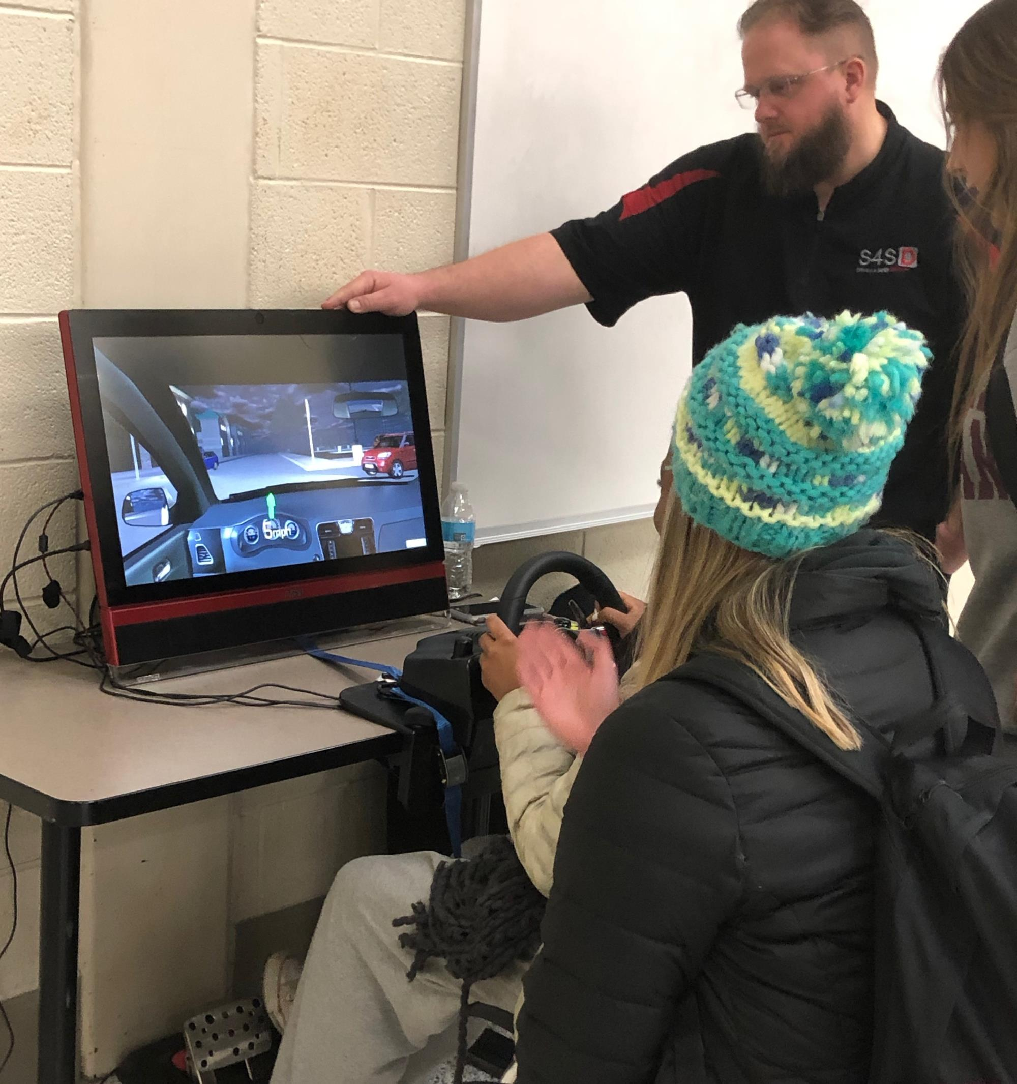 student sitting at a driving simulator
